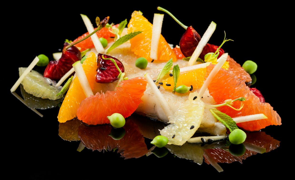 Daily Fish on a citrus fruits, fresh herbs and peas